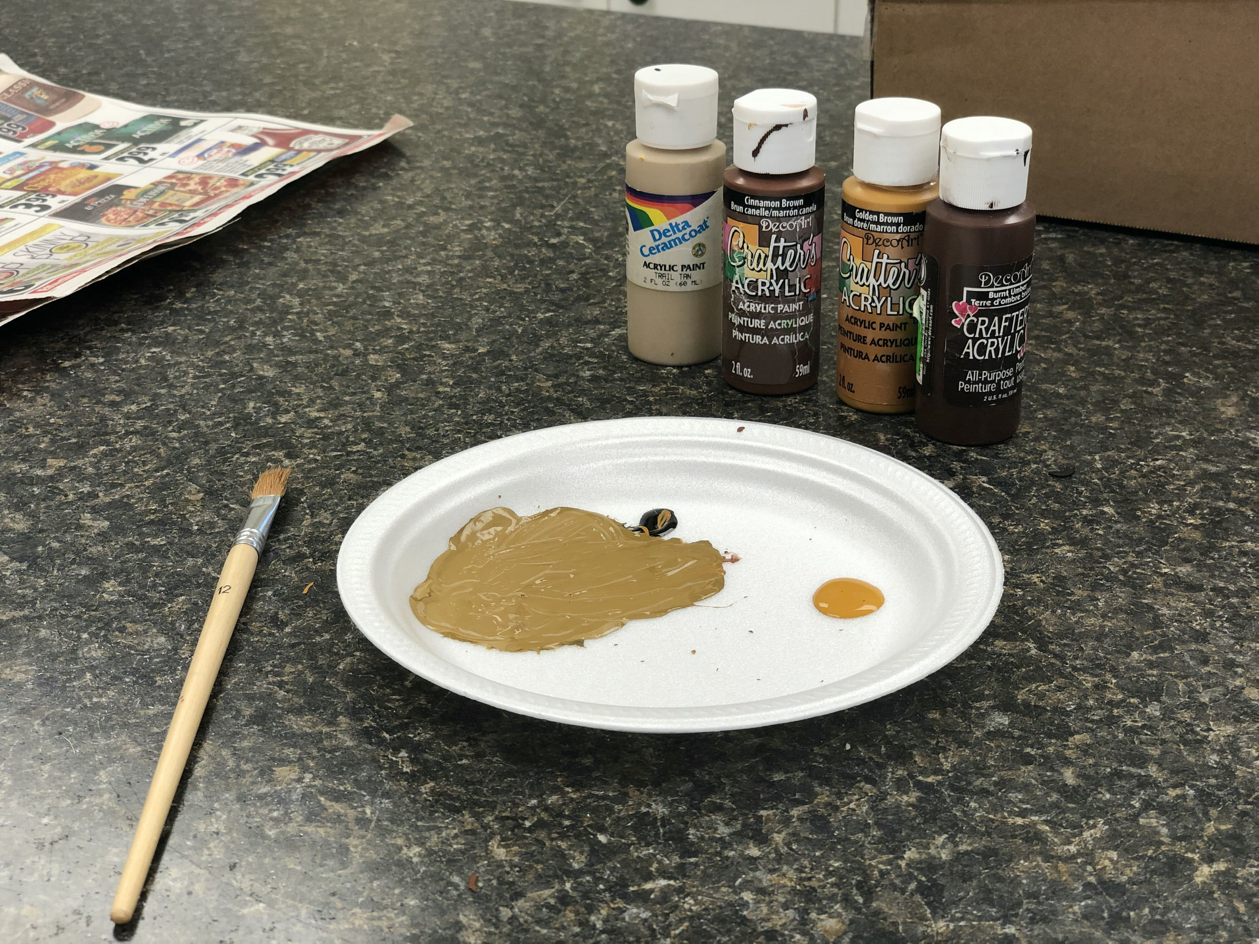 All four shades of brown paint used in this craft and a mixing tray and paintbrush in front of the paint with the colours that are going to be used to paint the popsicle sticks