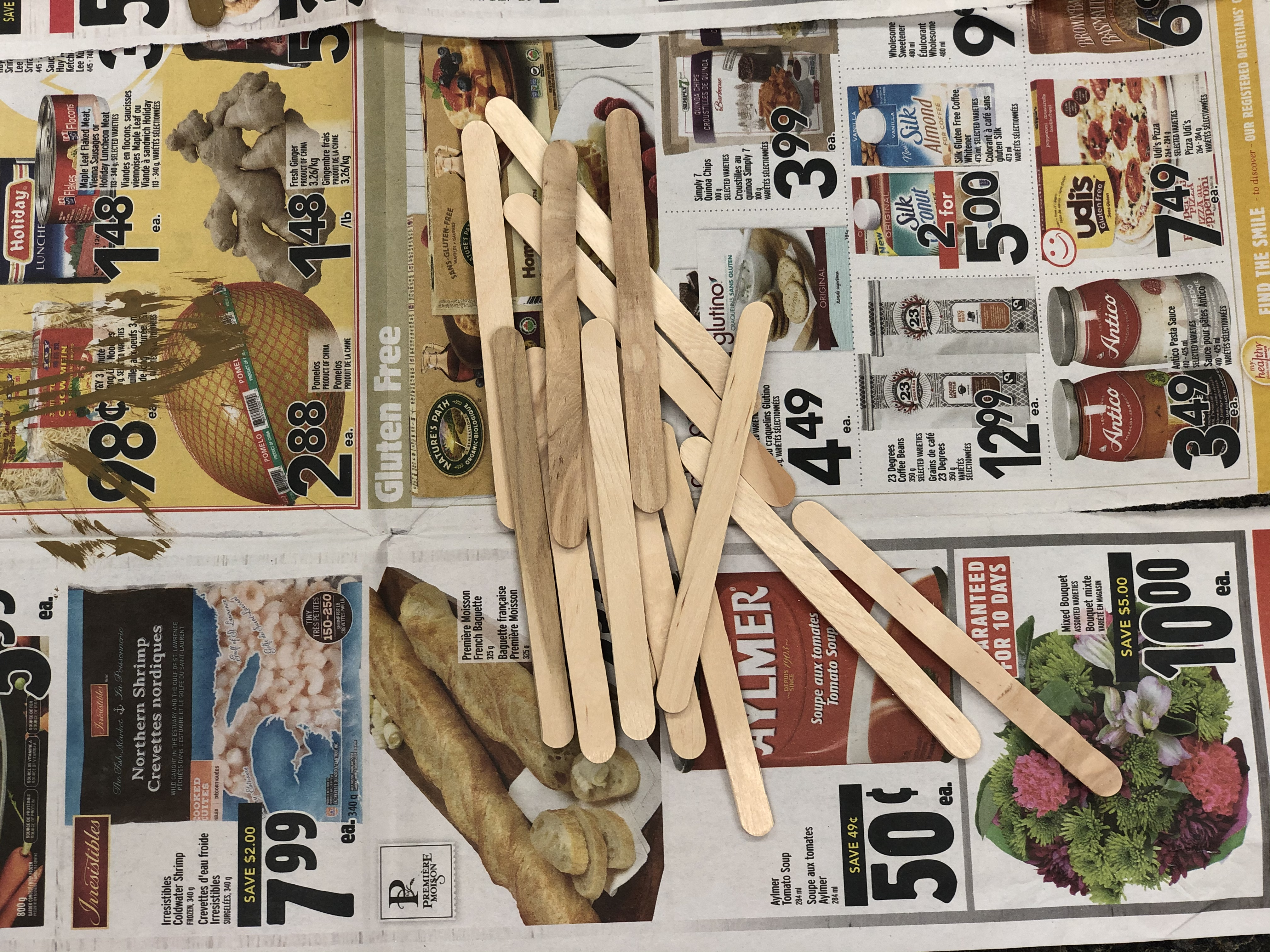 20 popsicle sticks layed out on newspaper before painting